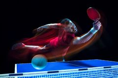 The table tennis player serving. The table tennis player in motion. Fit young sports man tennis-player in play on black background with lights. Movement, sport Royalty Free Stock Photos