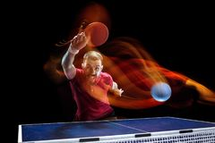 The table tennis player serving. The table tennis player in motion. Fit young sports man tennis-player in play on black background with lights. Movement, sport Stock Photo