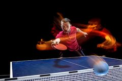 The table tennis player serving. The table tennis player in motion. Fit young sports man tennis-player in play on black background with lights. Movement, sport Royalty Free Stock Image