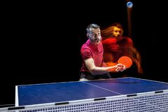 The table tennis player serving. The table tennis player in motion. Fit young sports man tennis-player in play on black background with lights. Movement, sport Royalty Free Stock Photography