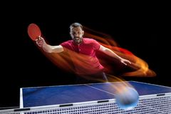 The table tennis player serving. The table tennis player in motion. Fit young sports man tennis-player in play on black background with lights. Movement, sport Stock Photos