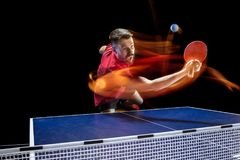 The table tennis player serving. The table tennis player in motion. Fit young sports man tennis-player in play on black background with lights. Movement, sport Royalty Free Stock Images