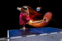 The table tennis player serving. The table tennis player in motion. Fit young sports man tennis-player in play on black background with lights. Movement, sport Stock Images