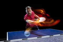 The table tennis player serving. The table tennis player in motion. Fit young sports man tennis-player in play on black background with lights. Movement, sport Stock Image