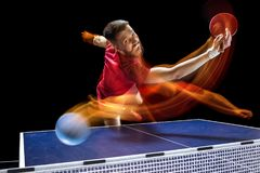The table tennis player serving. The table tennis player in motion. Fit young sports man tennis-player in play on black background with lights. Movement, sport Stock Photography