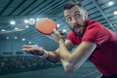 The table tennis player serving. The table tennis player in motion. Fit young sports man tennis-player in play on sport arena background with lights. Movement Stock Photos
