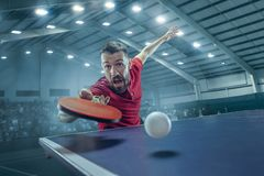 The table tennis player serving. The table tennis player in motion. Fit young sports man tennis-player in play on sport arena background with lights. Movement Royalty Free Stock Photo
