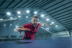 The table tennis player serving. The table tennis player in motion. Fit young sports man tennis-player in play on sport arena background with lights. Movement Royalty Free Stock Images