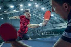 The table tennis player serving. The table tennis player in motion. Fit young sports men tennis-player in play on sport arena background with lights. Movement Stock Images