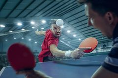 The table tennis player serving. The table tennis player in motion. Fit young sports men tennis-player in play on sport arena background with lights. Movement Royalty Free Stock Photography