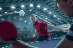 The table tennis player serving. The table tennis player in motion. Fit young sports men tennis-player in play on sport arena background with lights. Movement Royalty Free Stock Image