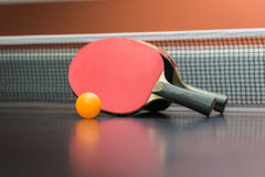 Table tennis racket with  ball on black table Stock Photos