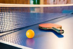 Table tennis - racket, ball, table. Tabletennis or ping pong rackets and yellow balls on blue table. Sport concept. Table tennis Stock Photography
