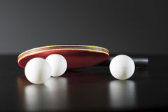 Table tennis racket and balls on dark table Royalty Free Stock Images