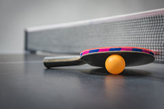 Table tennis racket with orange ball Royalty Free Stock Photography