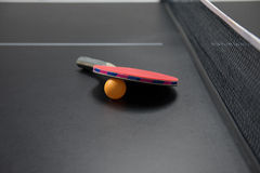 Table tennis racket with orange ball. On black table Stock Image