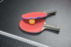 Table tennis racket with orange ball on black Royalty Free Stock Photography