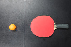 Table tennis racket with orange ball on black Royalty Free Stock Photos