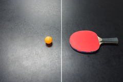 Table tennis racket with orange ball on table Royalty Free Stock Photos
