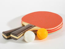 Table Tennis Racks. Two table tennis racks with a white and an orange ping pong ball Royalty Free Stock Images