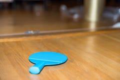 Table tennis racquet on wooden floor indoor Stock Photo