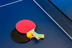 Table tennis table with rackets and orange ball royalty free stock photos