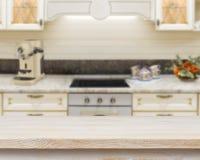 Table texturisée en bois au-dessus de fond brouillé d'intérieur de fourneau de cuisine Photos libres de droits