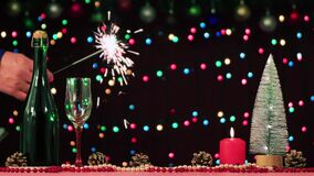 On the table there is champagne, a glass, a tree and cones, a candle is burning