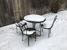 Table and three chairs in the snow Royalty Free Stock Photography