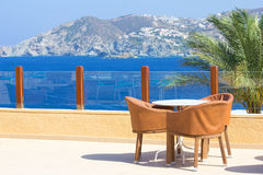 Table and three chairs on terrace with sea view royalty free stock photography