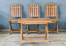 Table and three wooden chairs royalty free stock images