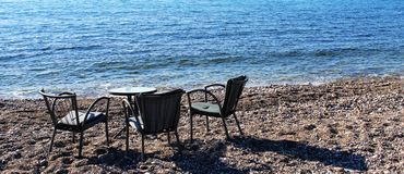 Table for three persons on a beach. The photo of a table for three persons on a sunny beach of Montenegro royalty free stock photos