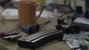 The table with tools. Place in a workshop for repair of weapons. Broken clips for ammunition. stock footage