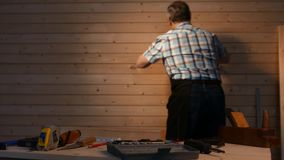 Table with tools in the workshop. Senior carpenter working in his workshop table with tools in focus stock footage
