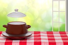 Table top on bowl background. Closeup of hot brown ceramic soup bowl on plate with lid on a red checkered tablecloth over blurred royalty free stock photos