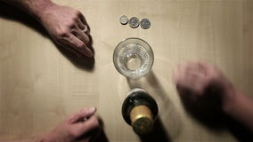Table top: buying a beer. Abstract, top down view of a pair of hands during a transaction as a man buys a bottle of beer from the other stock video footage