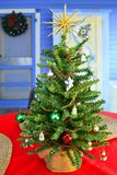 Table-Top Christmas Tree on the Porch. Small artificial Christmas tree on the table on the back porch of an early american home. There's a wreath on the door Royalty Free Stock Photos