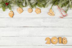 Happy New Year 2018. Table top shot of gingerbread cookies shaped as numbers 2018 with some fir branches, pine cones and christmas tree ornaments Royalty Free Stock Photos