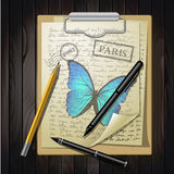 Table top with sketching paper and butterfly Royalty Free Stock Photo