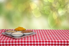 Table top on vegetable food background. Four bowls with buckwheat, noodles, rice and quinoa on a red checkered tablecloth over royalty free stock images