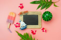 Table top view accessory plan to travel beach in summer holiday background concept. Flat lay  palm leaf with many essential items flower & palm leaf on pink stock photo