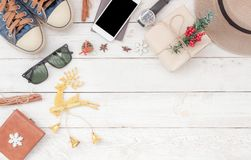 Table top view aerial image of accessories to travel on Merry Christmas & Happy New Year trip background concept. All object on modern rustic white wooden at Stock Photography