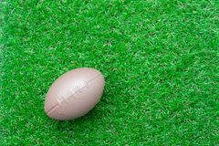 Flat lay object american ball on the artificial green grass royalty free stock images