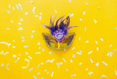 Table top view aerial image of beautiful colorful carnival season or photo booth prop Mardi Gras background. Flat lay object close up gold mask & confetti on stock photography