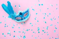 Table top view aerial image of beautiful colorful carnival season or photo booth prop Mardi Gras background. Flat lay object blue mask with confetti on modern stock photos