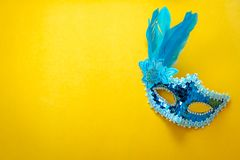 Table top view aerial image of beautiful colorful carnival season or photo booth prop Mardi Gras background. Flat lay object close up blue mask on modern yellow royalty free stock photos