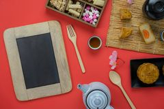 Table top view aerial image of decoration Chinese Moon Festival background. Concept.Flat lay Chinese food cake & tea and pink blossom on modern rustic red paper stock photography