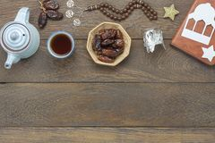 Table top view aerial image of decoration Ramadan Kareem holiday background. Flat lay date in wood basket with  rosary & green tea.Halal meal set for fasting is Stock Image