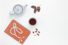 Table top view aerial image of decoration Ramadan Kareem holiday background. Flat lay dates with white rosary & cup tea.The holy book of Koran on modern white Royalty Free Stock Image