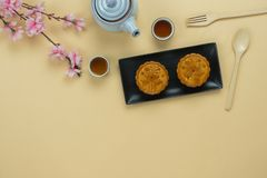 Table top view aerial image of decorations Chinese Moon Festival background concept. Flat lay cake & tea and pink blossom on modern rustic yellow paper royalty free stock images